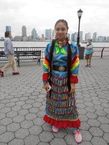 A Native American girl in traditional dress, there to welcome the Hōkūleʻa.